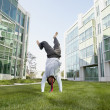 Businessman doing a handstand in the grass in front of office buildings - Stockfoto