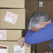 Businessman in warehouse with head down on returned packages - Stock Photo