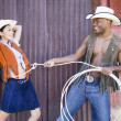 Young man in cowboy outfit lassoing his girlfriend - Foto Stock