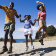 Family jumping for joy on the beach — Stock fotografie