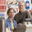 Father and daughter smiling for the camera in hardware store — Stock Photo