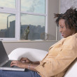 Young African woman sitting on sofa with laptop — Stock Photo