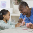 Senior woman playing cards with her granddaughter — Stock Photo #23245544