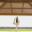 Woman doing yoga at beach resort — Stock Photo