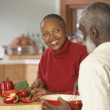Senior African couple chopping vegetables - Stock Photo