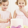Young girls picking at a birthday cake — Stock Photo
