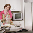 Young woman baking as she talks on the phone — Stock Photo