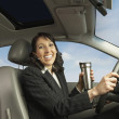 Businesswoman driving with travel mug — Stock Photo