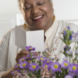 Senior woman reading a card — Stock Photo #23245930