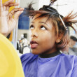 Young woman checking her hair in beauty salon - Stock Photo
