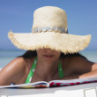 Woman wearing a straw hat and reading a magazine on the beach — Stock Photo