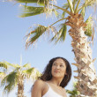 Hispanic woman in bathing suit next to palm trees - Stock Photo