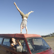 Man doing a handstand on car roof - Stock Photo