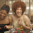 Two young African women laughing at a dinner party — Stock Photo #23246088