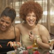 Two young African women laughing at a dinner party - Stock Photo