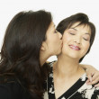 Studio shot of adult Asian daughter kissing mother on cheek - Stock Photo