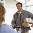 Woman signing for packages from deliveryman — Stock Photo #23246204