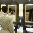 Man in robe in front of bathroom mirror — Stock Photo