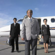 Three businesspeople standing next to airplane - Stock Photo