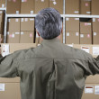 Businessman in warehouse looking at stacks of packages — Stok fotoğraf