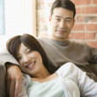 Couple relaxing on the couch together - Stock Photo