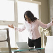 Businesswoman standing at her desk - Stock Photo