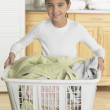 Young girl holding a laundry basket - Stock Photo