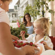 Woman offering strawberries to young child - Stock Photo