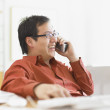 Businessman talking on the phone at his desk - Stock Photo