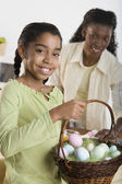 Portrait of girl holding Easter eggs in basket with mother looking at her — Stok fotoğraf