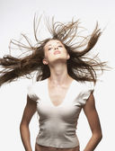 Portrait of woman whipping hair around — Stock Photo