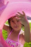 Portrait of girl looking through inner tube — Stock Photo