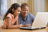 Mother and daughter using computer together — Stock Photo
