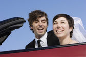 Portrait of bride and groom in convertible — Stock Photo