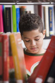 Young boy reading in library — Stock Photo