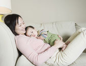 Asian mother and baby on the sofa — Stock Photo