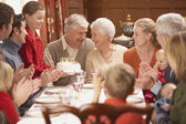 Grandmother with birthday cake and family at dinner table — Stockfoto
