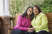 Mother and daughter smiling on a porch swing — Stock Photo