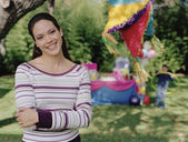 Young woman smiling for the camera at a child's birthday party — Foto Stock