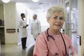 Senior female nurse with doctors in background — Stock Photo