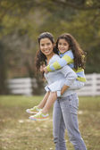 Hispanic mother giving her daughter a piggy back ride — Stock Photo