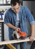 Carpenter sawing wood — Stock Photo