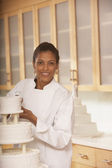 African female pastry chef next to a wedding cake — Stock Photo