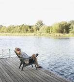 Hombre de mediana edad relajante en silla por lago — Foto de Stock