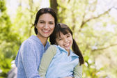 Hispanic mother and daughter smiling outdoors — Stock Photo