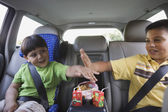 Young boys high-fiving in the backseat — Stock Photo