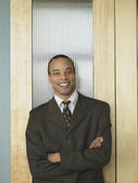 African businessman leaning on an office door — Stock Photo