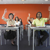 Adults raising their hands in classroom — Stock Photo