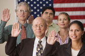 Adults raising their right hands before American flag — Stock Photo