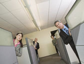 Businesspeople peeking out of office cubicles — Stock Photo